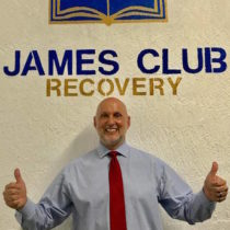 Ray Rapaglia posing beneath James Club Recovery Sign